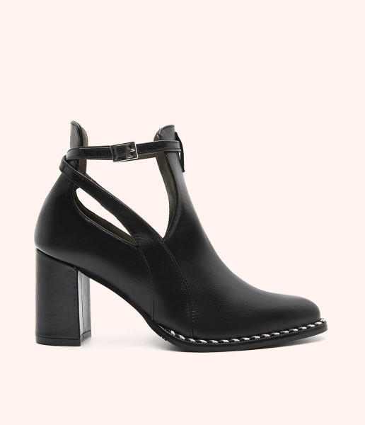 Leather ankle boot with side openings, ankle buckle and heel.